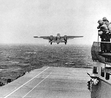 Black and whiteimage of the B-25 taking off of the aircraft carrier at sea.