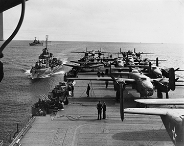 Black and white image of airplanes on an aircraft carrrier at sea.