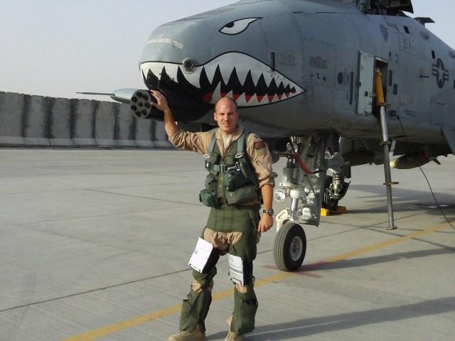 Caucasian male in uniform in front of plane