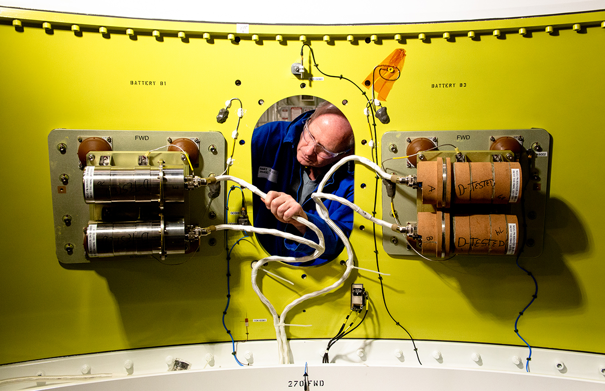 A Northrop Grumman engineer installs batteries on an OmegA first stage aft skirt. (March 2019)