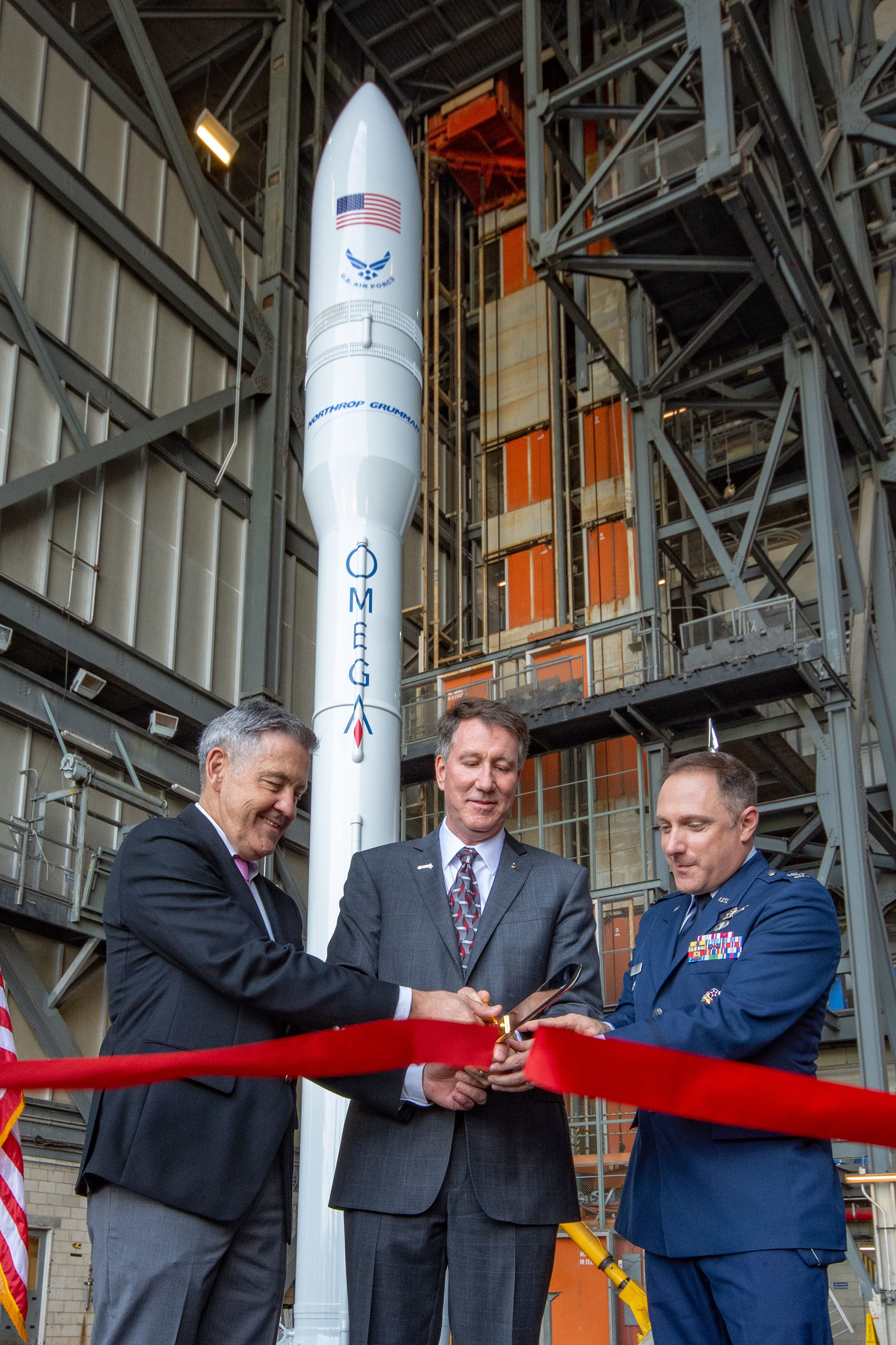 "Three men in suits cutting ribbon with large scissors with OmegA rocket behind them"" title=""OmegA Ribbon Cutting at VAB"