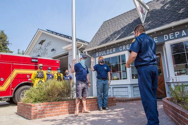 Two white men are sworn in as volunteer firefighters outside
