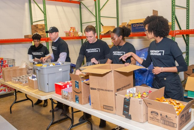 Several Northrop Grumman employee volunteers package food at a table