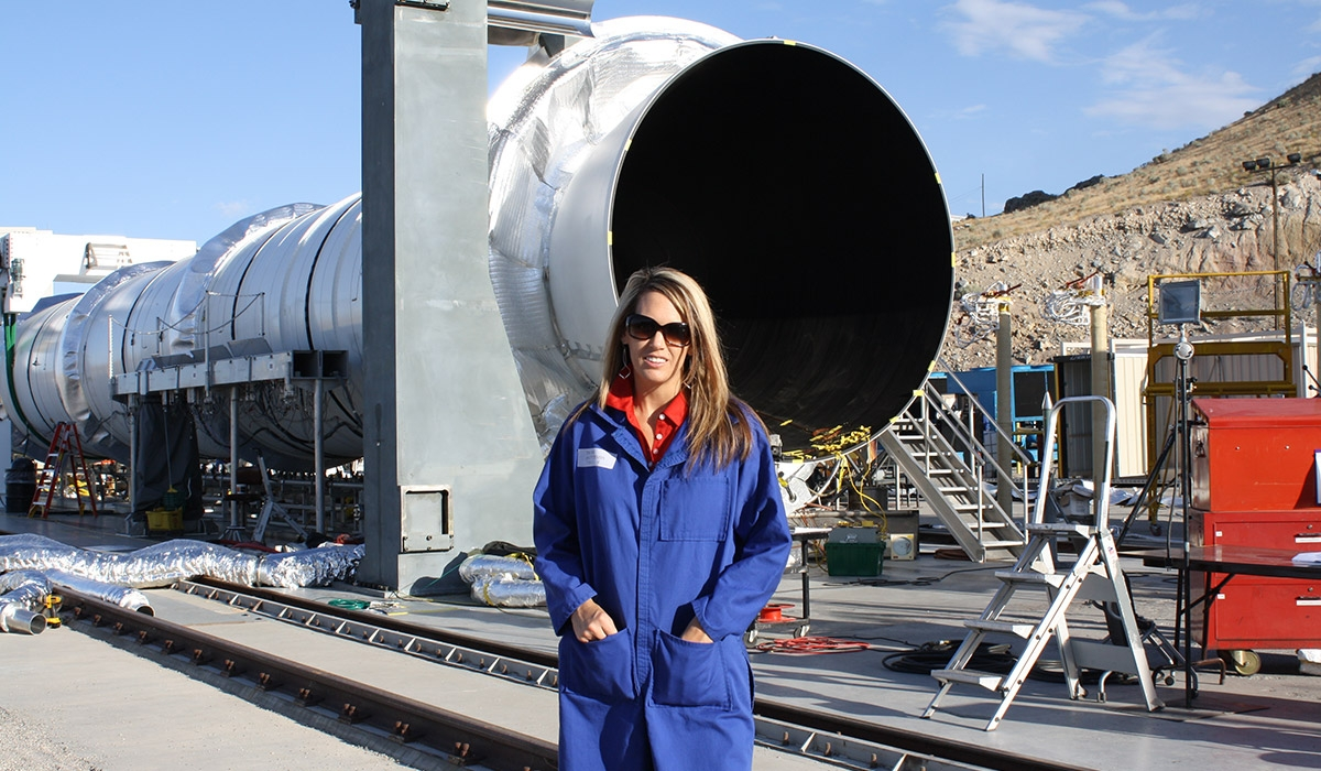 Caucasian woman poses outside in front of OmegA rocket booster