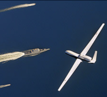 A military plane flying over the ocean with a ship sailing below
