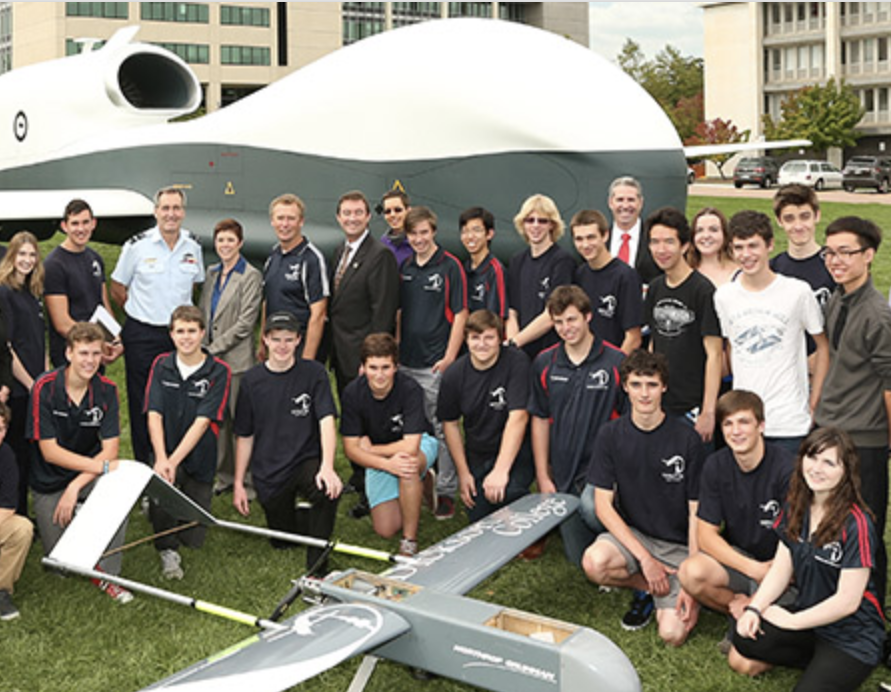 Young students gather around aircraft