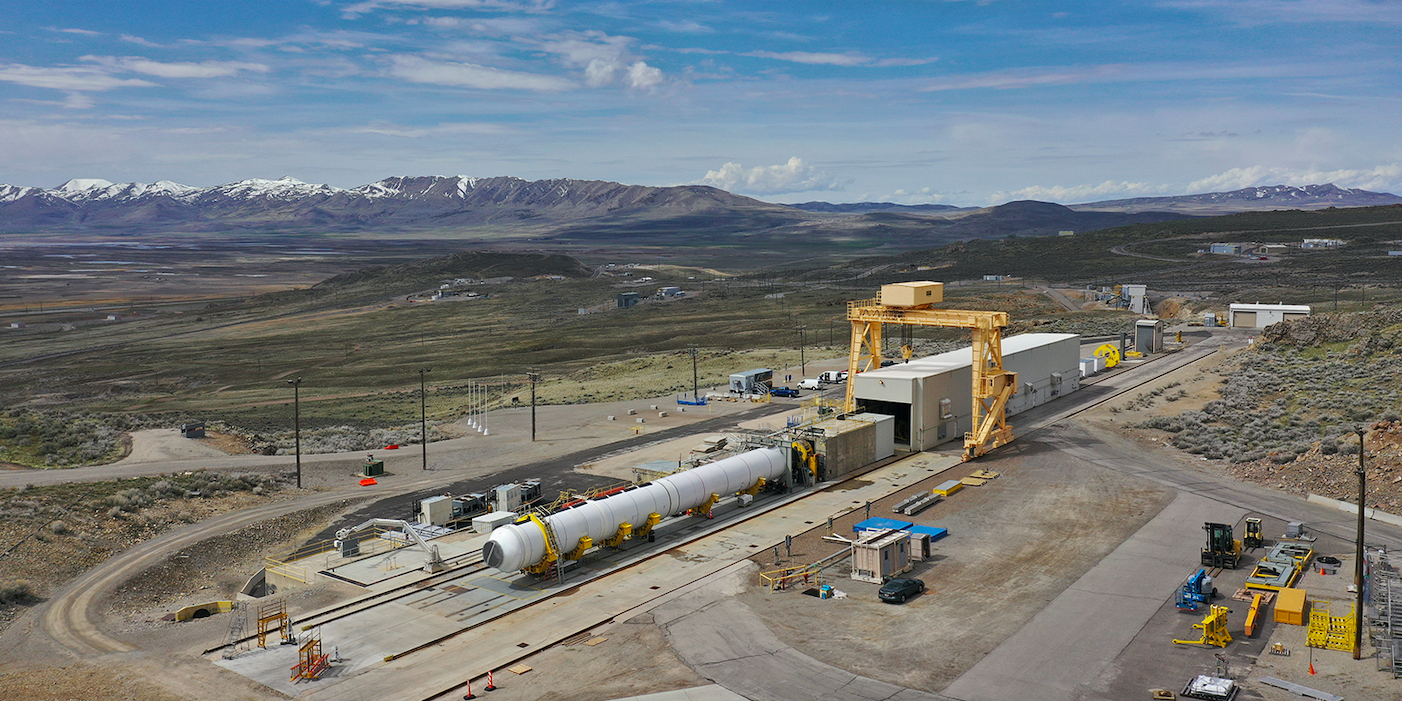 rocket motor in test stand with mountains