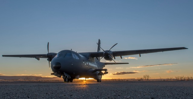 Military aircraft with sunset behind it