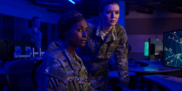 A black woman and a white woman in army suits in a control room.