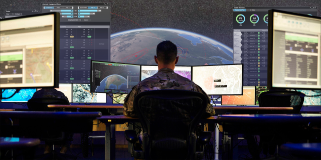 A white man looking at computer screens in a control room