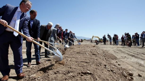 People lined up in a row using shovels to dig in dirt.