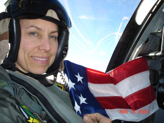 Female pilot in uniform, sitting in the cockpit with American flag in background