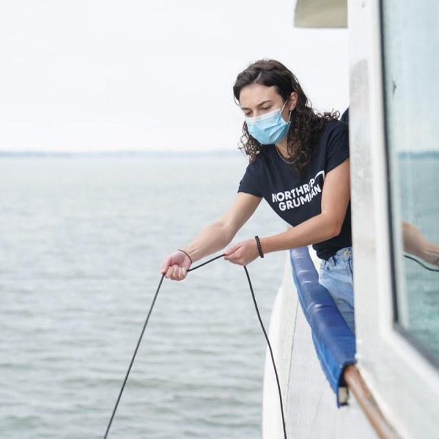 female Northrop Grumman employee holding line in water on boat