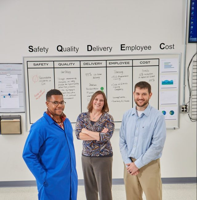 Two males and one female standing in front of white board
