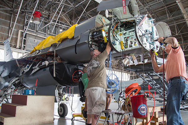 men working on front of military aircraft in hangar