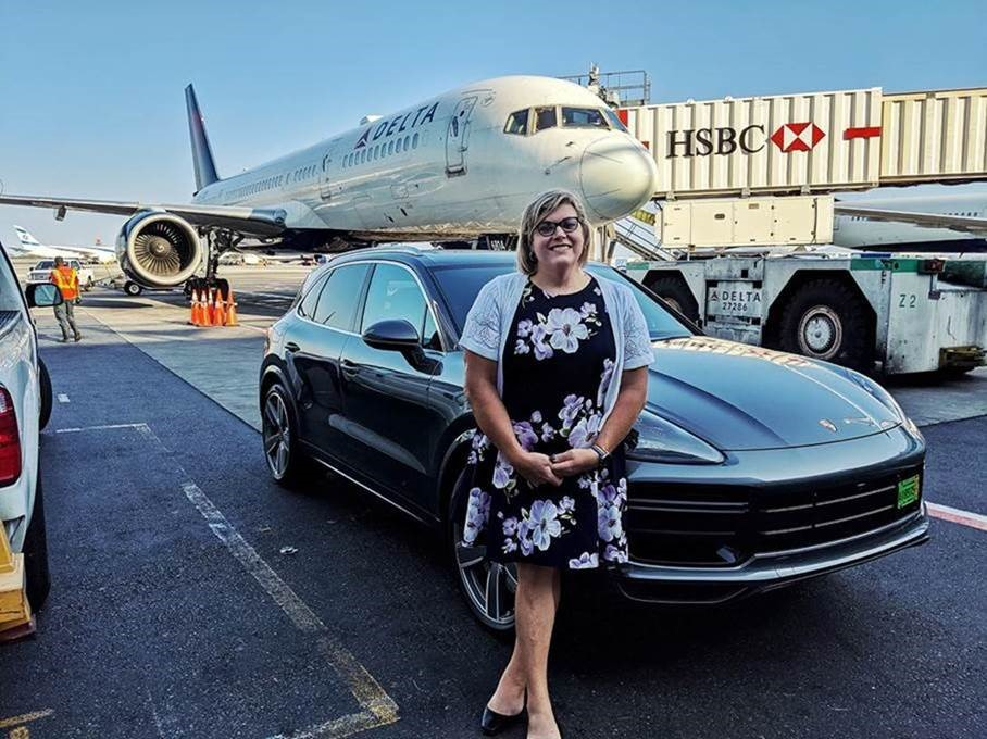 Woman in front of car and airplane