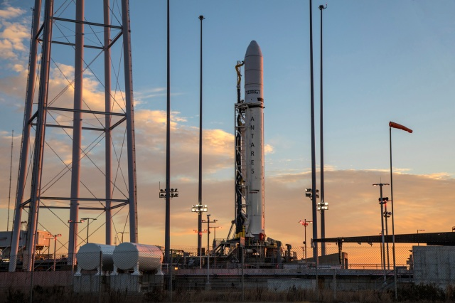 A rocket on launch pad at sunrise in front of a partial blue lit sky as sun comes up