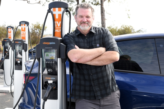 A older white gentleman standing with arms crossed next to an electric vehicle charger station.