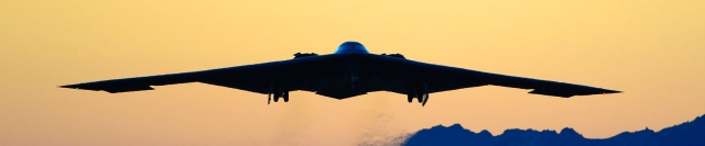 B-2 Spirit airplane flying at dusk with mountain range in background.