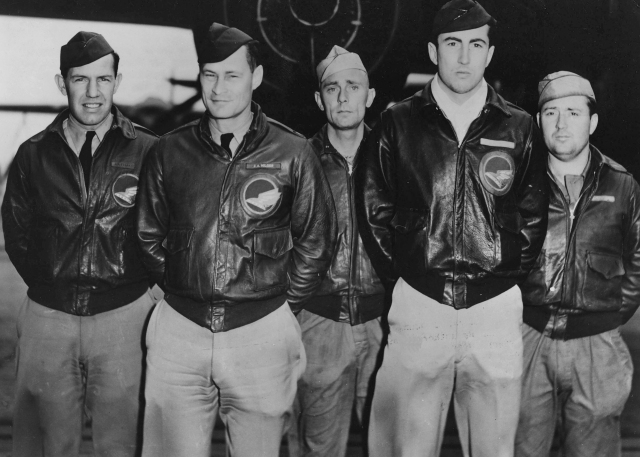 Five pilots standing in front of a plane for a group picture