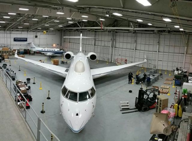 Interior of hanger with white jet looking head-on