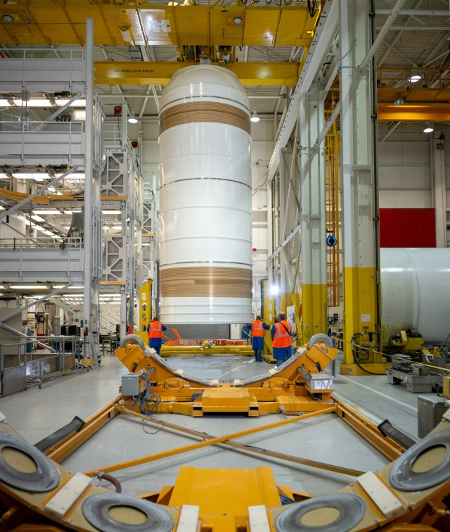 a solid rocket booster stands on end in a hangar
