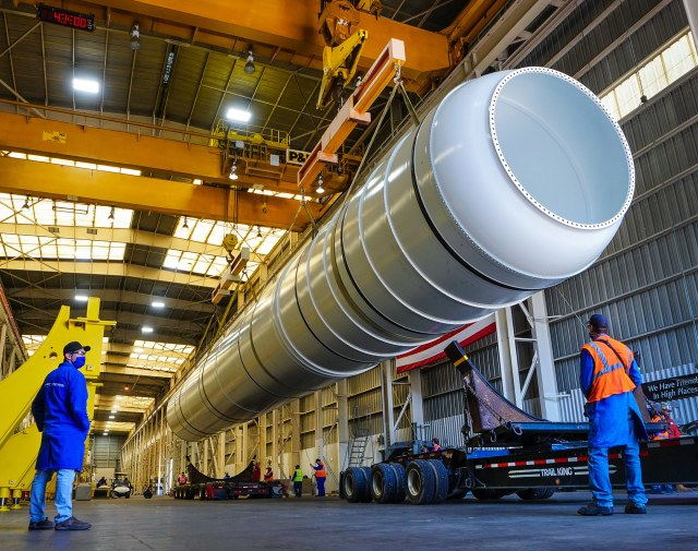 a solid rocket booster being loaded on a trailer