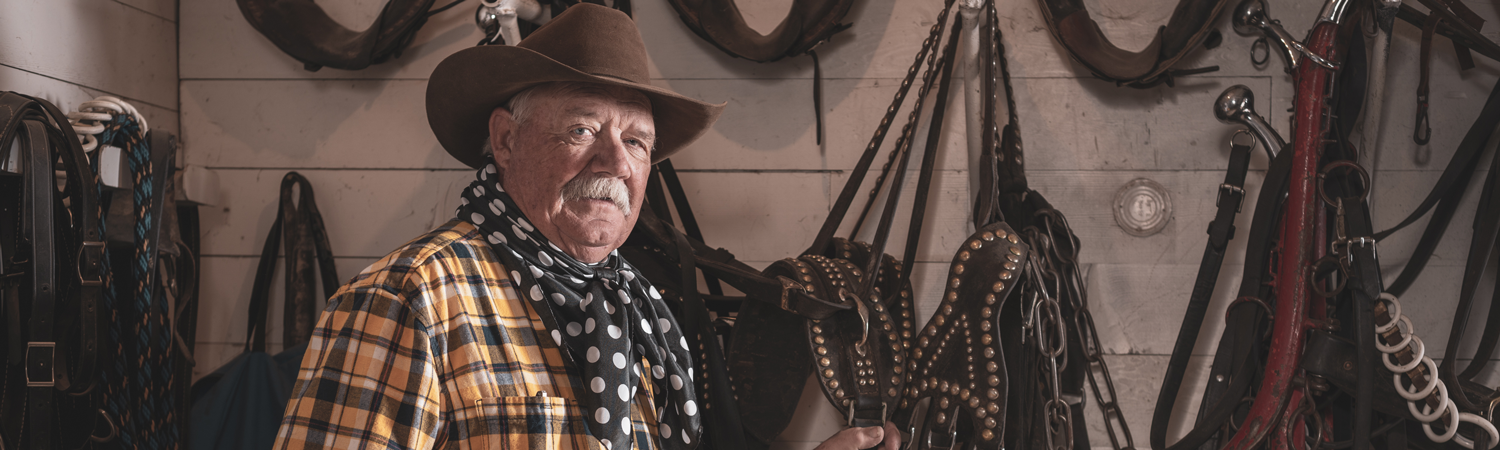 Older Caucasian man in cowboy attire poses in front of horse saddles hanging on wall