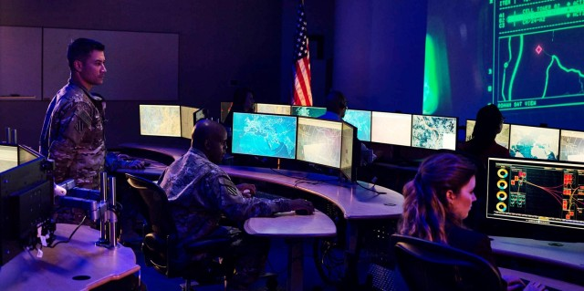 5 people in dark lit control room looking at computer screens dressed in military camouflaged suits and business attire