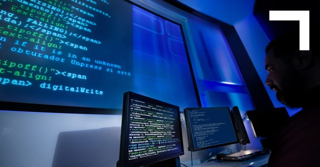 man looking at large computer screen with code