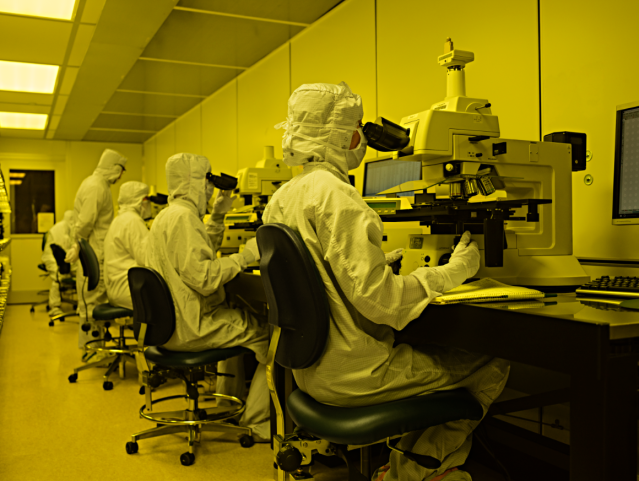Employees in lab attire use microscopes in a lab
