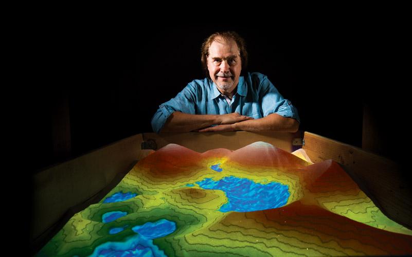 Headshot of man peering over virtual reality sandbox with water and mountains