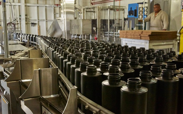 man watching an assembly line of powder cannisters