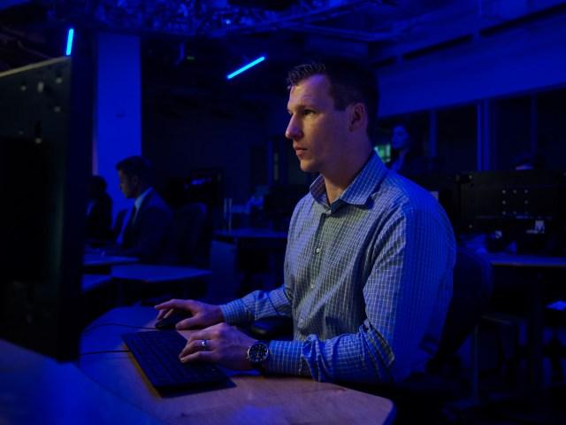 man sitting at computer desk in darkend room