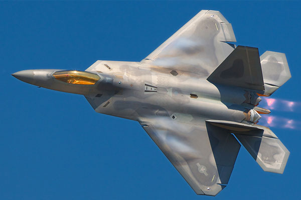 military fighter jet flying in blue sky