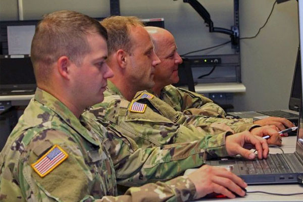 three white men in military uniforms on laptops