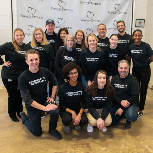 Employees volunteering at food bank wearing black t-shirts