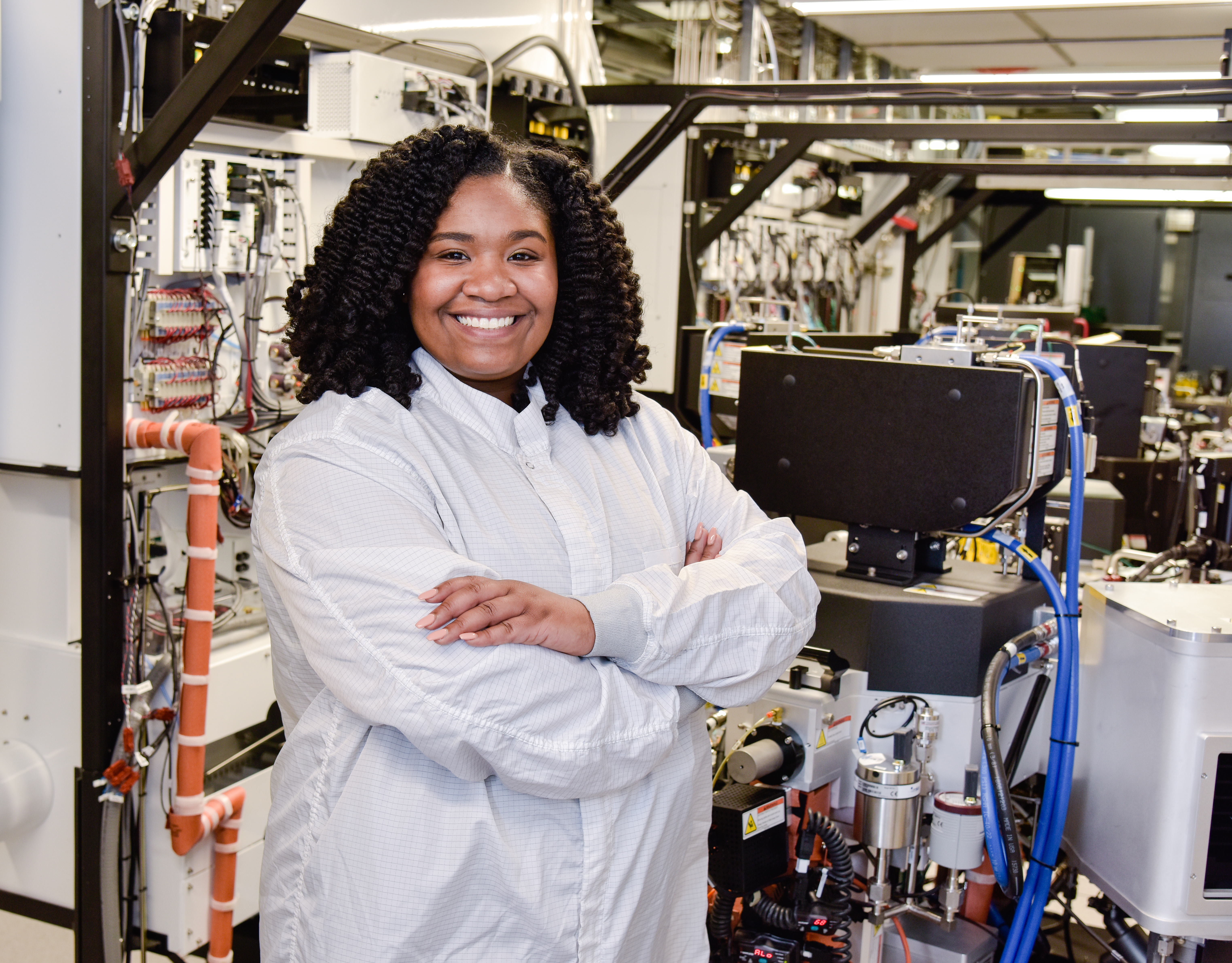 Young African American woman wearing lab attire stands smiling in lab
