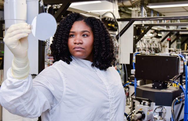 Young Black woman in lab attire examine an object in a lab
