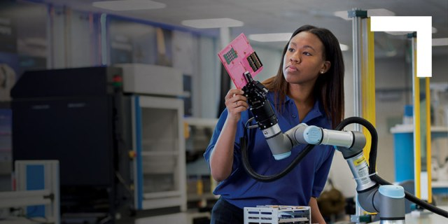 black woman holding robotic arm