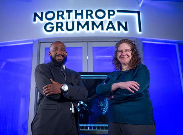 A black man and white woman smile at the camera with a Northrop Grumman logo in the background