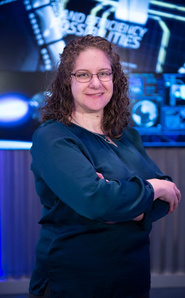 A white woman stands with her arms crossed in front of a computerized background