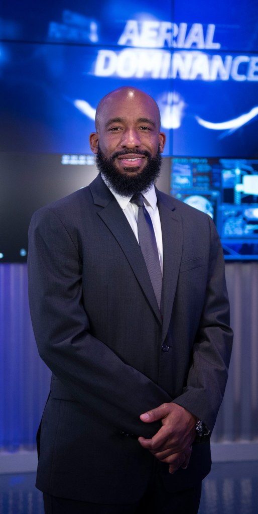 A black man in a suit stands in front of a computerized background