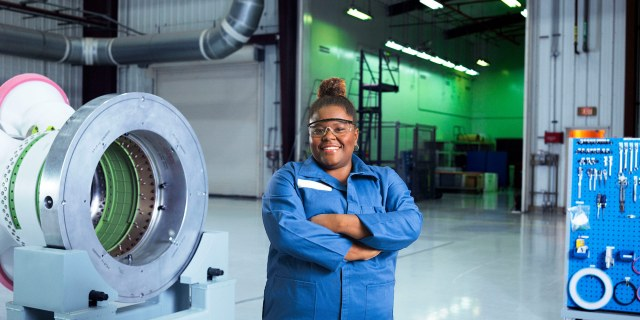 black female employee in blue jumpsuit in space facility