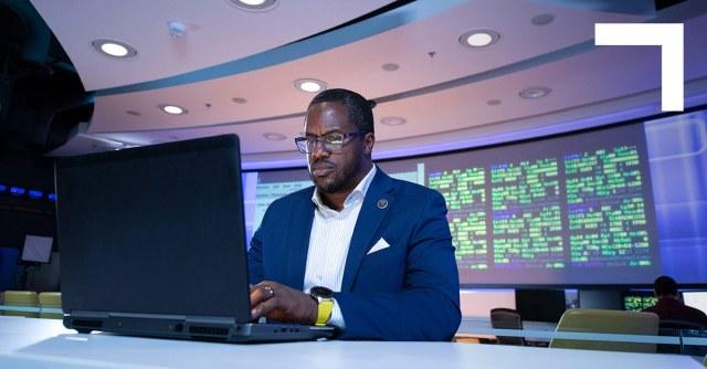 black man in suit on laptop