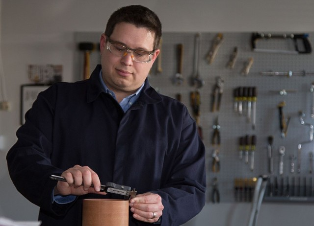 White man wearing safety goggles works in workshop