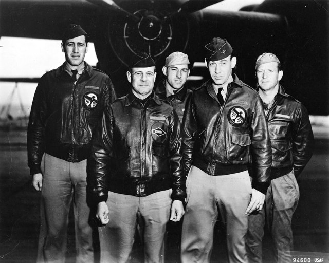 five men in leather coats in front of military plane