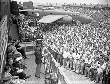 Black and white image of a man in military uniform giving a speech to a crowd outdoors and next to a jet.