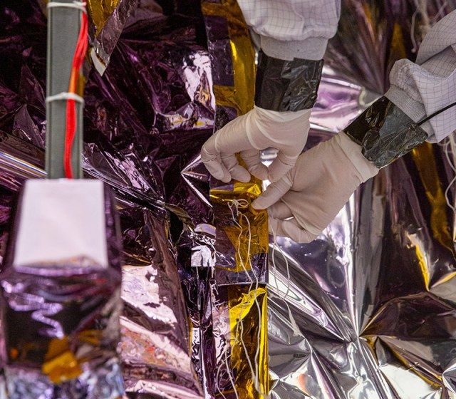 two hands carefully applying materials to spacecraft