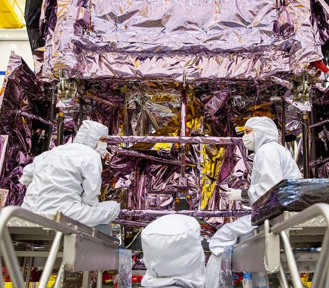 Three workers dressing spacecraft
